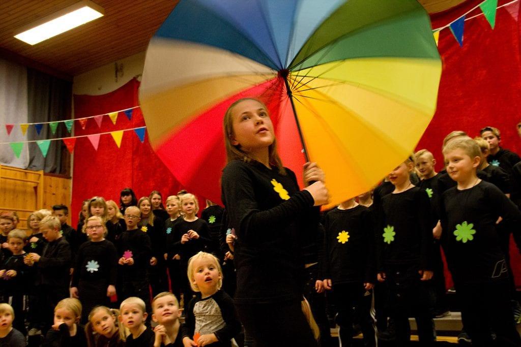 FARGERIK: Skolekoret feiret Fåset skoles 10 første år med en fargerik og flott konsert tirsdag kveld. Her svever Sanna Hektoen forbi, mens koret synger Singing in the Rain. Foto: Anne Skjøtskift