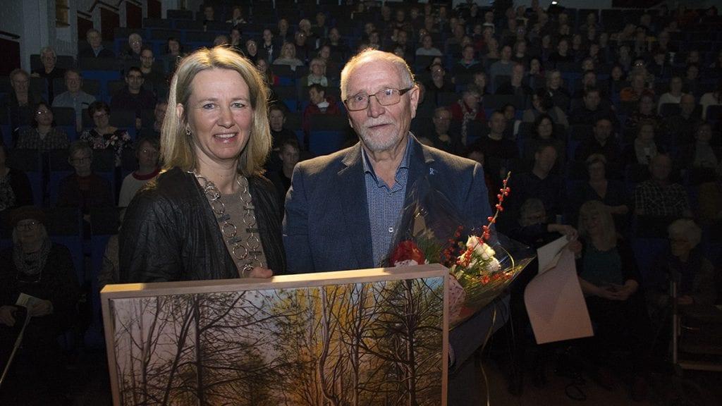 OVERRASKET OG GLAD: Ellef Røe strålte over alle de varmeordene og prisen han fikk overrakt av ordfører Merete Myhre Moen. Foto: ToreRasmussen Steien