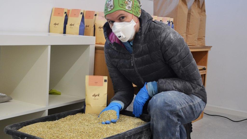 HÅNDARBEID: Ingrid F. Gardseth demonstrerer at mye av jobben fra korn til mjølposene er håndarbeid. Foto: Erland Vingelsgård