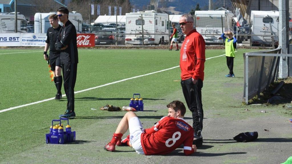 OVER OG UT: En liggende Kjetil Skorstad Thoresen, dette bildet er fra 3. divisjonsoppgjør mot Lillehammer i 2017, har nå fått så mange skader at karrietren er over. Pappa Svein Per Thoresen (til høyre, og hovedtrener Mats Lund får ytterligere en utfordring med dette. Foto: Jan Kristoffersen