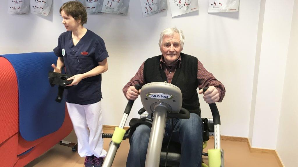KJEMPEGAVE: Erik Kindølshaug tester det nye treningsapparatet mens fysioterapeut Berit Nordstad takker for den flotte gaven. Foto: Jan Kristoffersen
