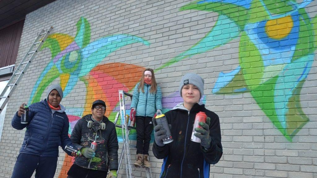 VAKKERT: Nagiib Kosar (fra venstre), Rodriges Lisboa, Emilie Taraldsteen og Amund Fjæran foran den fint dekorerte øst-veggen på Tynset barneskole. Foto: Erland Vingelsgård