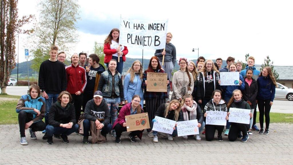 KLIMASTREIK: Rundt tretti elever fra Nord-Østerdal videregående skole gjennomførte klimastreik fredag. Mange musikkelever var med i gruppa, så flerstemt sang stod også på programmet til aksjonistene. Foto: Anne Skjøtskift
