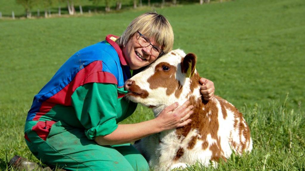 KOS: Anne Marit Grøtli liker å kalle seg Autorisert bondekone på Grøtlitoppen, og stortrives sammen med dyra sine. Kalven Olga og alle de andre får mye kos. Foto: Anne Skjøtskift