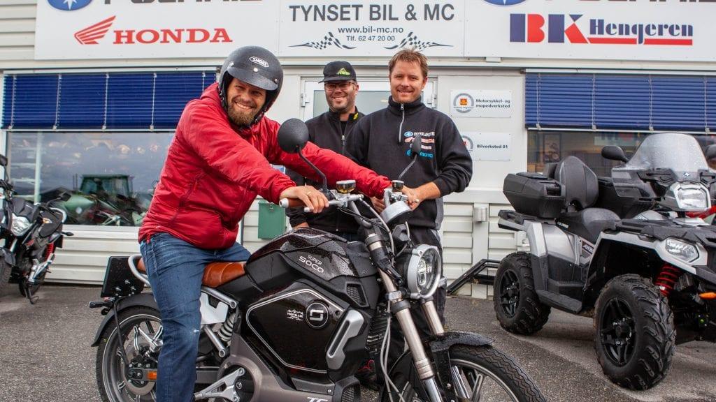 EL-GLIS: Sindre Sørhus i Tynset MDG likte godt prøveturen han fikk med den elektriske mopeden fra Tynset Bil & MC. Mopeden til ca 30 000 kr har oppgitt ti mil rekkevidde per batteri, som det er plass til to av. Sindre Sørhus (t.v) diskuterte el-kjøretøy med Knut Bjørkeng (t.h.) og Roar Bangen. Foto: Lars Vingelsgård